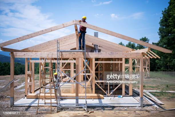 construction workers working on wooden roof of house. - construction industry stock pictures, royalty-free photos & images