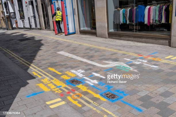 Construction workman and multi-coloured aerosol-sprayed markings on the ground, in a side-street off Long Acre near Covent Garden, are on 23rd June...