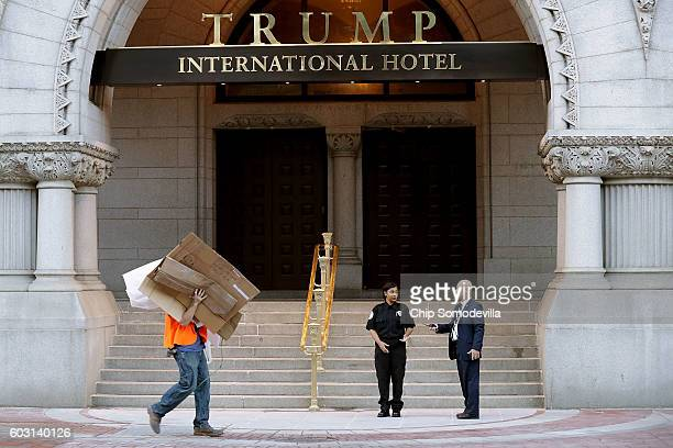 Construction works clear away debris in front of the Trump International Hotel on the first morning it is open for business September 12 2016 in...