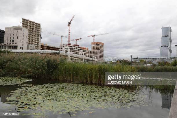 Constructions sites are seen behind the Martin LutherKing garden in the Batignolles area on September 5 2017 in Paris / AFP PHOTO / LUDOVIC MARIN