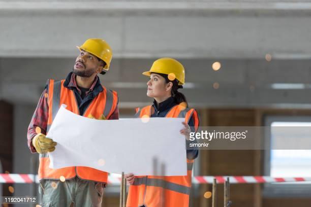 bauarbeiter diskutieren blaupause - the black tape project stock-fotos und bilder