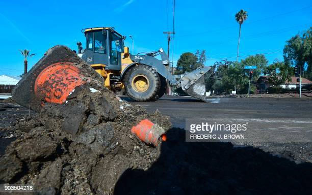 A constrution vechile clearing the road drives past mud along La Tuna Canyon Road in Sun Valley neighborhood of Los Angeles California on January 10...