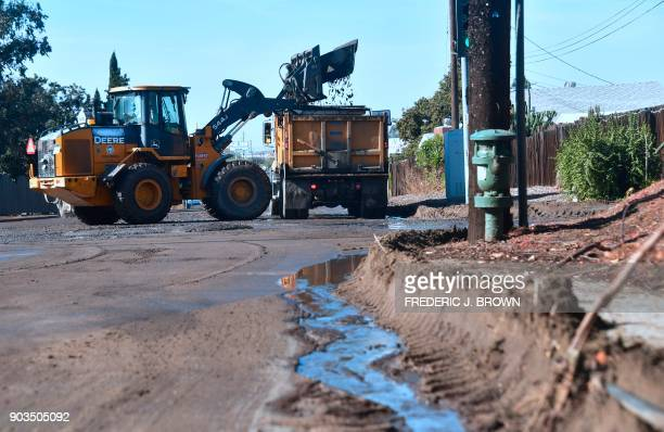 A constrution vechile clears mud along La Tuna Canyon Road in Sun Valley neighborhood of Los Angeles California on January 10 2018 The death toll...