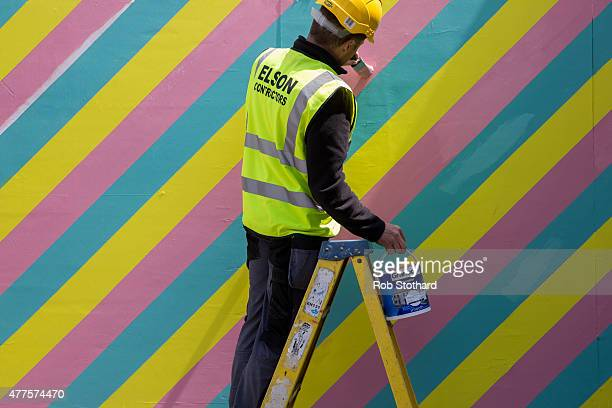 A constrution worker paints a sign at Dreamland amusement park on June 18 2015 in Margate England Dreamland is considered to be the oldestsurviving...