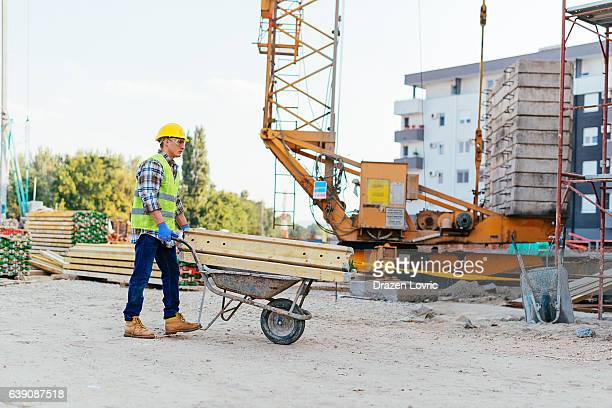 consturction worker pushing wheelbarrow on construction site - wheelbarrow stock photos and pictures