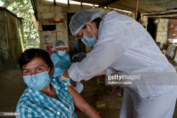 Consuelo Londoño Pulecio a nursing assistant, gives Maria Eugenia Diaz a shot of the first dose of Sinovac COVID-19 vaccine at her house during a...