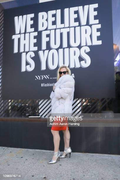 Consuelo Vanderbilt a white Costin coat and a red Kimor Lee Simmons dress on the street during New York Fashion Week on February 9 2019 in New York...