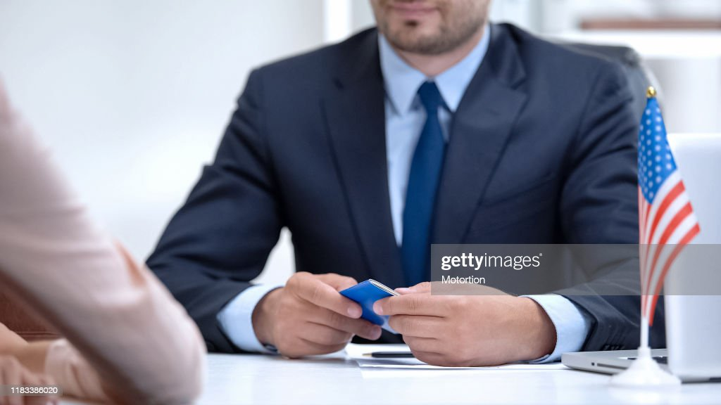 Consular officer of USA holding passport of female immigrant, citizenship visa : Stock Photo