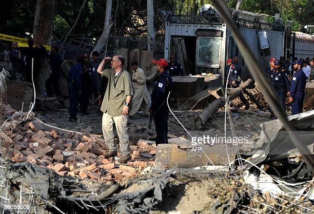 US consulate officials look at the damaged portion of the main entrance of their consulate following a huge suicide bomb attack in Peshawar on April...