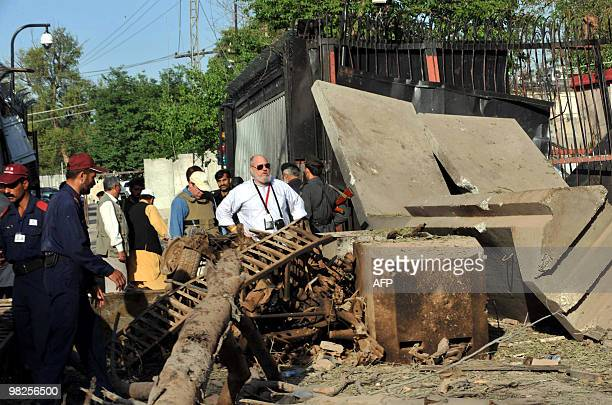 US consulate officials look at the damaged portion of thei consulate's main entrance following a suicide bomb attack in Peshawar on April 5 2010...