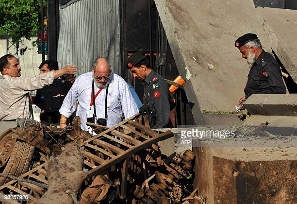 US consulate officials look at the damaged portion of their consulate's main entrance following a suicide bomb attack in Peshawar on April 5 2010...