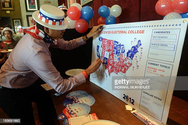 A US consulate staff member marks a US map in Republican and Democrat colours as the results of the US Presidential elections are announced during a...