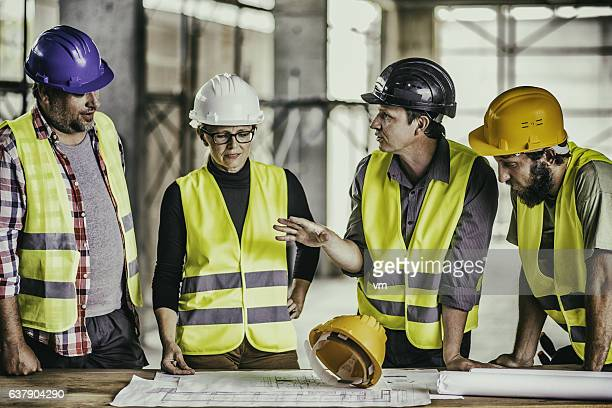 Consulting about blueprints on a reconstruction site