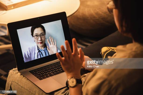 consulting asian doctors online using laptop - telemedicine stock pictures, royalty-free photos & images
