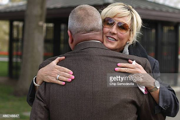 Consumer advocate Erin Brockovich embraces retired Master Sgt Jerry Ensminger during a small rally on Capitol Hill April 23 2014 in Washington DC...