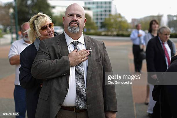 Consumer advocate Erin Brockovich leans on breast cancer survivor Mike Partain as he recites the Pledge of Allegiance during a small rally on Capitol...