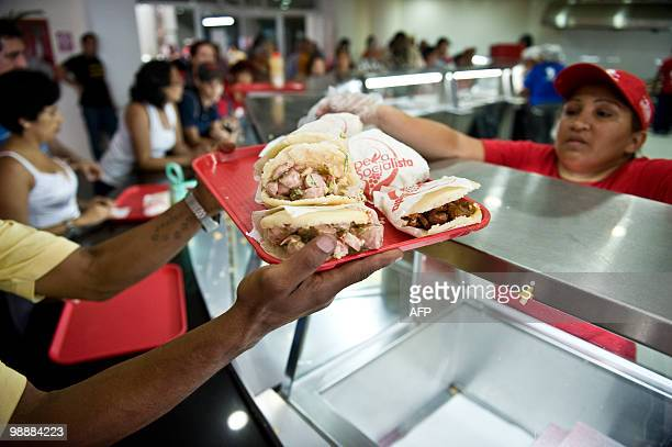 ABREU A consumer buy 'arepas' at a Socialist Arepera restaurant in Caracas on April 30 2010 The 'Socialist Areperas' are one of the new state retail...