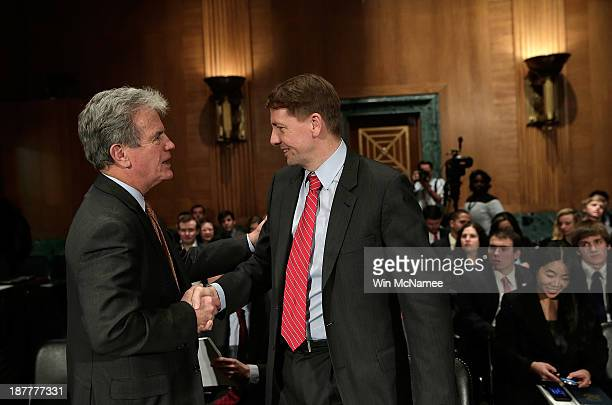 Consumer Financial Protection Bureau Director Richard Cordray talks with Sen Tom Coburn prior to his testimony before the Senate Banking Housing and...