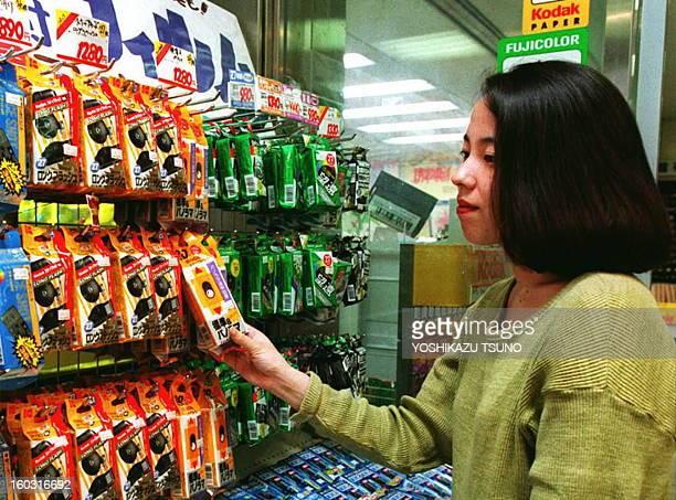 A consumer inspects a disposable camera made by Kodak among Fuji and Konica products at a Tokyo camera shop 14 June The US Trade Representative...