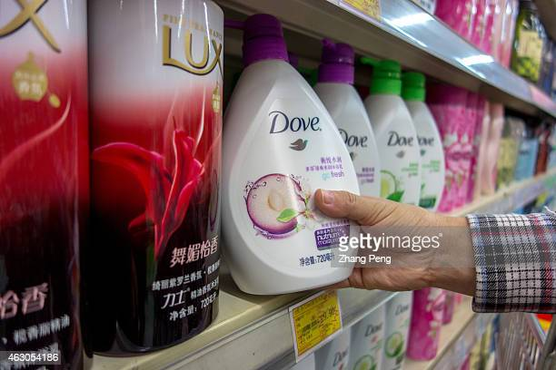 A consumer is choosing a Dove bath foam in a Chinese supermarket Dove is one of the brands of Unilever Hit by the slowdown of China's economy sales...