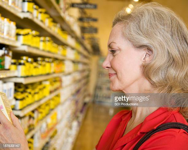 Consumer Reading Medication Box in Drug Aisle at Grocery Store