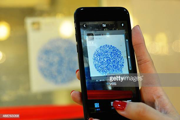 A consumer scans the QR to pay at a local market on September 14 2015 in Wenzhou Zhejiang Province of China Over 70 stalls in a local market started...