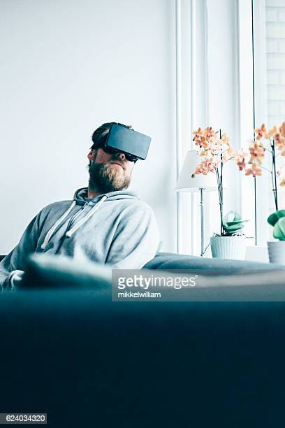 Consumer sits in sofa at home and wears VR glasses
