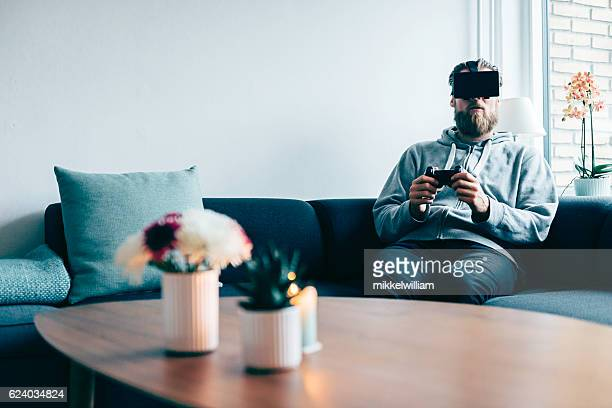 Consumer wears VR glasses and holds controller for a game