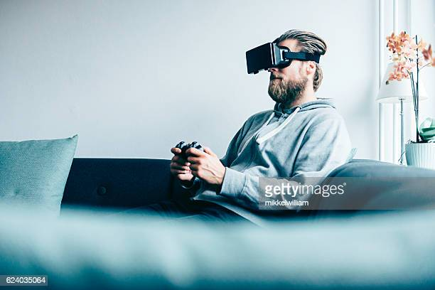 consumer wears vr glasses and plays game at home - electrical equipment stock photos and pictures