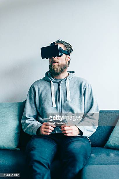 Consumer wears VR glasses at home and plays game