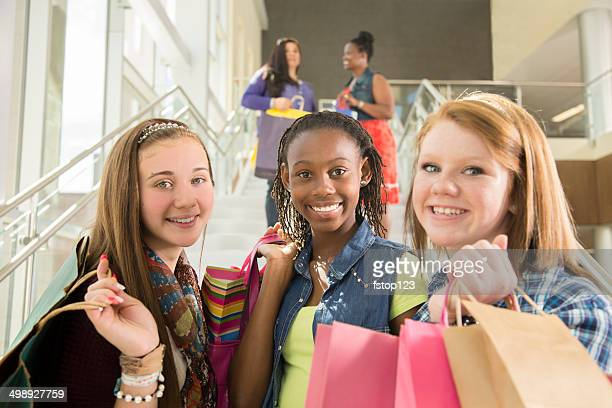 Consumerism: Mixed-race girlfriends shop in mall with shopping bags.