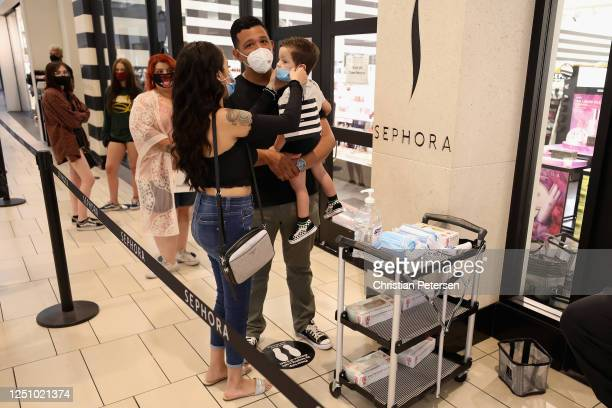 Consumers apply face masks as they stand in line for 'Sephora' at the Arrowhead Towne Center on June 20 2020 in Glendale Arizona Arizona is one of...