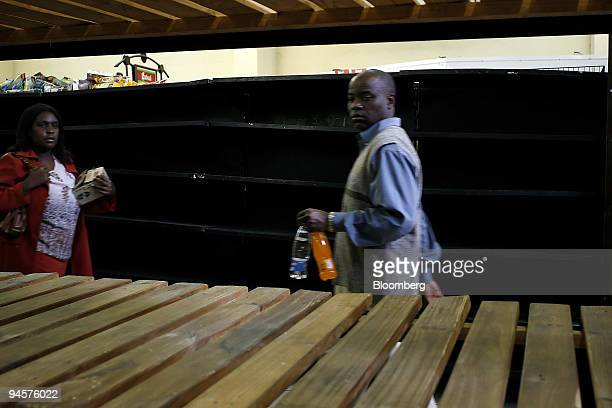 Consumers carry items found in an otherwise empty supermarket in Harare Zimbabwe Monday July 23 2007 Zimbabwe's government extended price controls in...