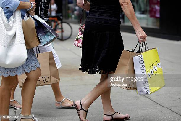 Consumers hold shopping bags as they walk along Michigan Avenue on July 29 2016 in Chicago Illinois The US economy grew by 12% in the second quarter...