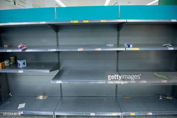 Consumers leave shelves empty in a London Morrisons store as panicbuying over coronavirus continues on March 14 2020 in London England Members of the...