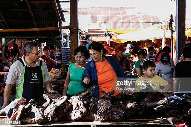 Consumers look at wild boar meat at Langowan traditional market on August 9 2014 in Langowan North Sulawesi The Langowan traditional market is famous...