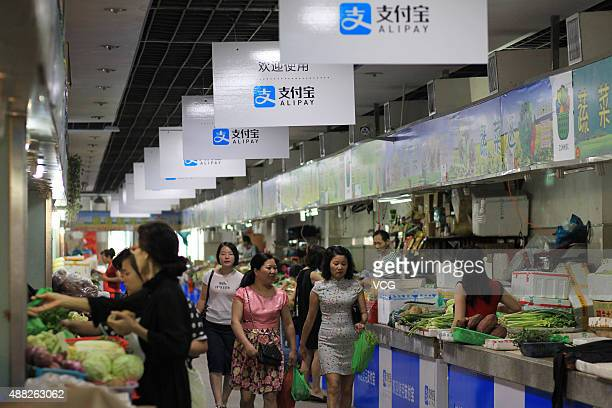 Consumers purchase at a local market with boards of Alipay hung up on September 14 2015 in Wenzhou Zhejiang Province of China Over 70 stalls in a...
