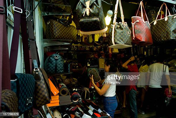 Consumers select fake Louis Vuitton handbags at Chatuchak Weekend Market on December 1 2012 in Bangkok Thailand The Chatuchak Weekend Market also...