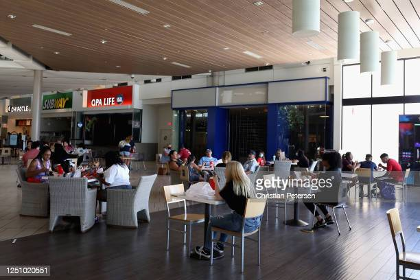 Consumers sit in the food court as they return to retail shopping at the Arrowhead Towne Center on June 20 2020 in Glendale Arizona Arizona is one of...