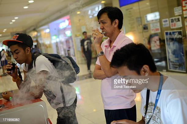 Consumers smoke electronic cigarettes at a mall on June 30 2013 in Manila Philippines Electronic cigarettes are gaining popularity among former heavy...