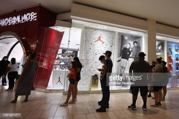 Consumers stand in line to enter 'Shoe Palace' as they return to retail shopping at the Arrowhead Towne Center on June 20, 2020 in Glendale, Arizona....