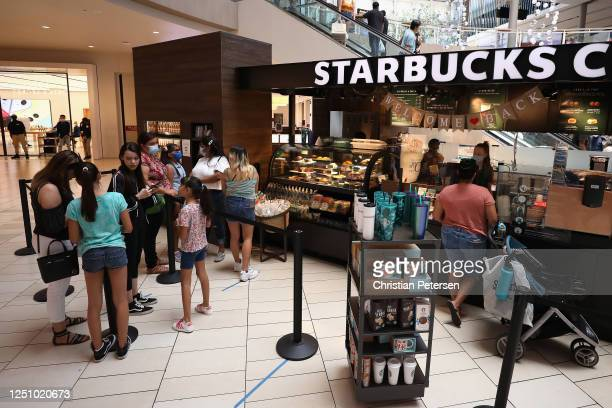 Consumers wait in line at a Starbucks location as they return to retail shopping at the Arrowhead Towne Center on June 20 2020 in Glendale Arizona...