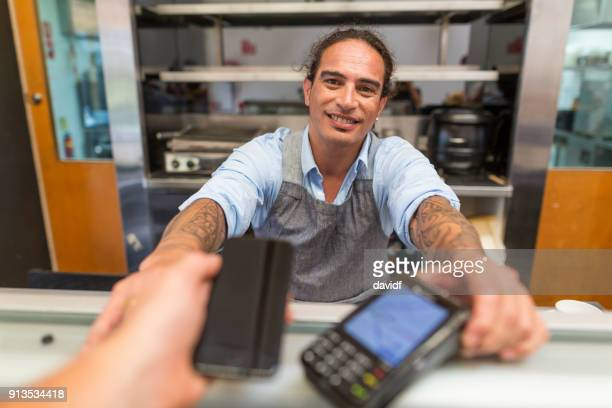 contactless credit card payment with a phone in a cafe business - minority groups stock pictures, royalty-free photos & images