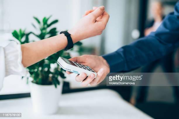 kontaktloses bezahlen mit smartwatch - kleine uhr stock-fotos und bilder
