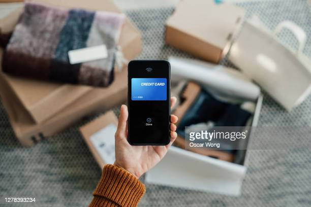 contactless payment - close up shot of hand holding smartphone with online shopping box stack at the background - paying stock pictures, royalty-free photos & images