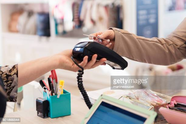 "contactless payment for woman shopping in a children store. - ""martine doucet"" or martinedoucet stock pictures, royalty-free photos & images"