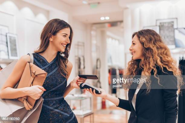 contactless payment in a luxury fashion store - boutique stock photos and pictures