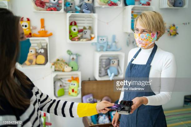contactless payment in a small business store during coronavirus pandemic. - assistant stock pictures, royalty-free photos & images
