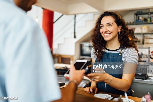 contactless payment in coffee shop - paying stock pictures, royalty-free photos & images