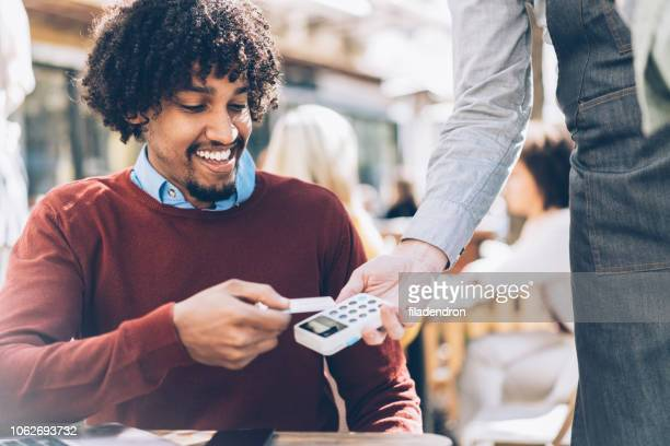 handsome afroamerican man paying contactless with